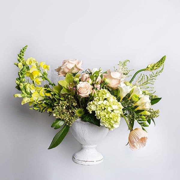 vase arrangement yellows pinks stone